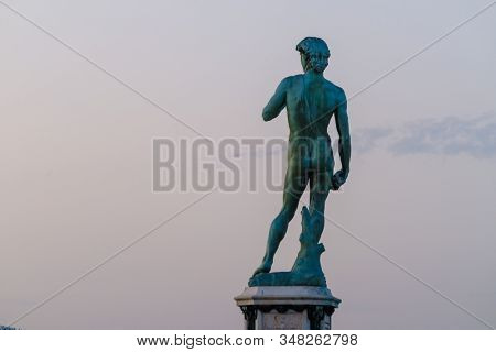 Florence, italy - August 12, 2019: Aged Statue of David mounted on pedestal on Piazzale Michelangelo against hill and sundown sky in evening