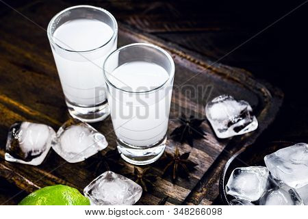 Ouzo Or Uzo, Is A Greek Anise Brandy, Traditional Strong Alcoholic Drink In Glasses On The Old Woode
