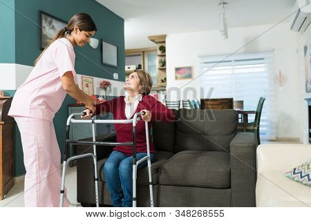 Confident Nurse Helping Senior Disabled Woman To Walk With Mobility Walker At Home