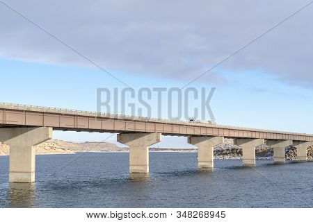 Stringer Bridge Supported By Abutments Ovelooking Lake Land And Cloudy Sky