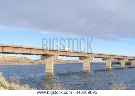 Truck On A Stringer Bridge Acroos Blue Lake Overlooking Hills And Cloudy Sky