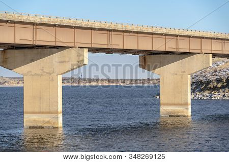 Focus On A Beam Bridge Supported By Abutments Over Blue Lake Against Cloudy Sky