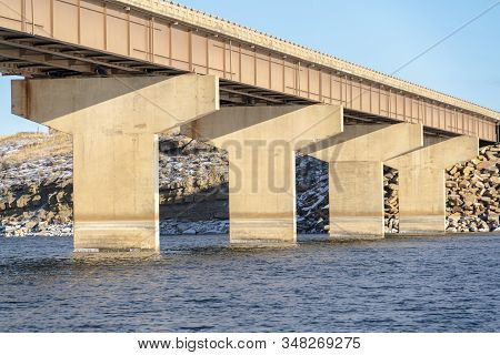 Massive Abutments Supporting The Span Of A Beam Bridge Over Blue Lake Water