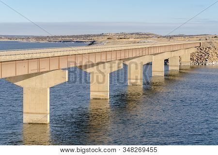 Stringer Bridge Spanning Over Calm Lake With View Of Snowy Land And Cloudy Sky