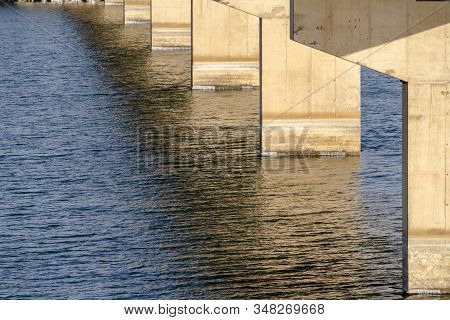 Views Underneath A Beam Bridge With Abutments Against The Sunlit Lake Water