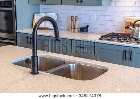 Double Bowl Sink And Black Faucet On Kitchen Island Against Cooktop And Counter