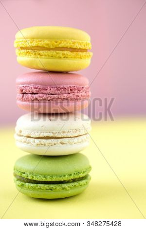Pink, yellow, white and green traditional french macaroons on pink and yellow background
