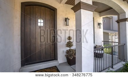 Panorama Brown Wood Arched Front Door With Glass Panes At The Facade Of Home With Porch
