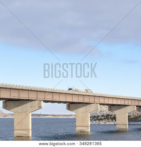 Square Frame Stringer Bridge Supported By Abutments Ovelooking Lake Land And Cloudy Sky