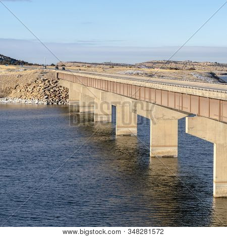 Square Beam Bridge With Deck Supported By Abutments Or Piers Spanning Over Blue Lake