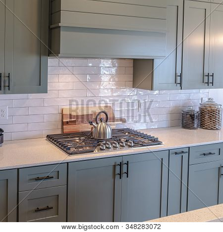 Photo Square Frame Wooden Cabinets And White Counter Top Inside A Kitchen With Tile Backsplash