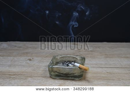 Smoking On A Wooden Table With Smoke Floating In The Concept Of Relaxation And Addiction.