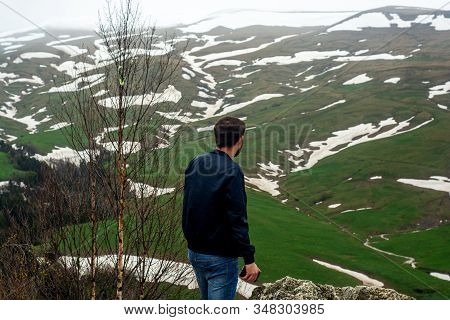 Back View Of A Male Tourist Who Travel In Mountains With Green Landscape Of High Tableland With Rest