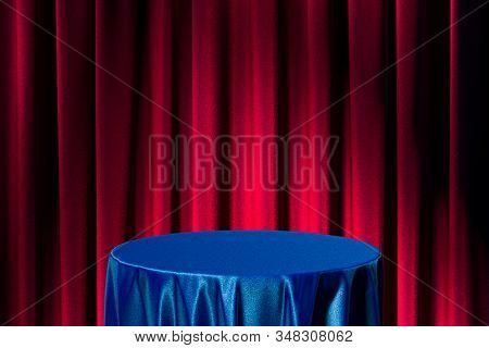 Table With Blue Cloth On Red Curtains Background. 3d Rendering