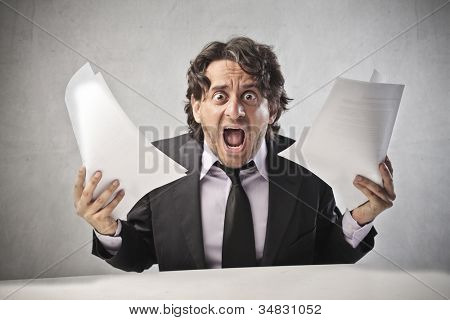 Screaming businessman holding some documents