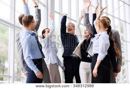 corporate and teamwork concept - happy business team making high five or celebrating success at office