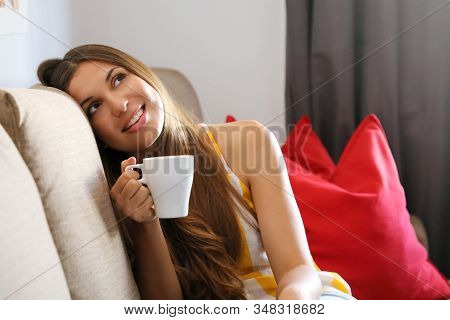 Young Smiling Woman Sitting On Sofa And Looking Up While Drinking Hot Tea. Girl Dreaming Or Thinking
