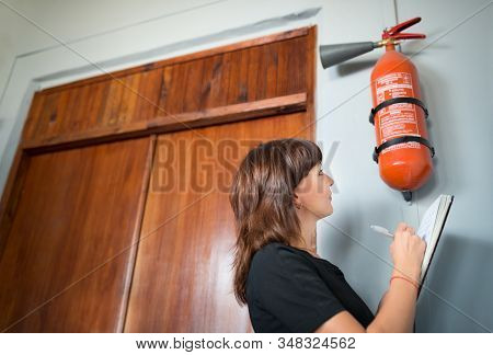 Young Woman Fire Inspector Writes An Office Inspection Review Certificate On A Wall With A Fire Exti