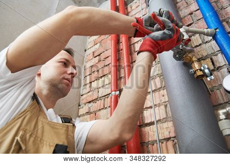 plumber installing water equipment - meter, filter and pressure reducer