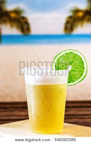 Glass Of Cold Drink, With Beach In The Background. Refreshing Drink, Carioca Mate Tea, Made In The C