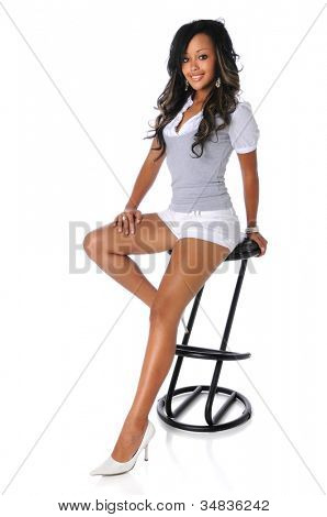 Young African American woman sitting on stool isolated over white background