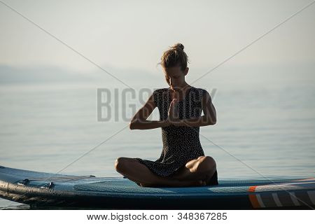 Young Woman Meditating With Her Hands Joined On Her Chest, Sitting On Sup Board Floating On Calm Mor