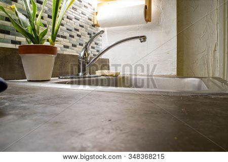 Pov Shot On Cement Countertop With Sink And Plant In Background