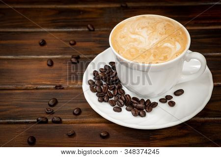 Cappuccino In A White Glass On A Saucer. Coffee Beans On A Saucer. Brown Background