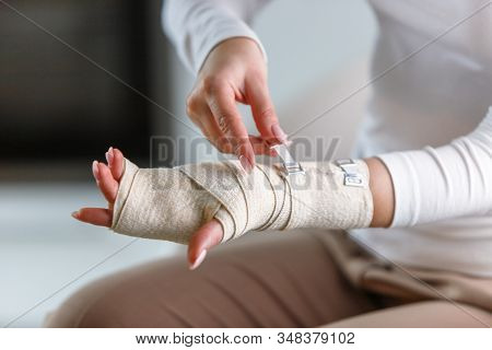Close Up Of Woman Wrapping Her Painful Wrist With Flexible Elastic Supportive Orthopedic Bandage Aft