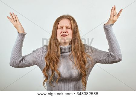 A Young Unhappy Woman With Red Hair Raises Her Hands In Despair And Misery In Gray Sweater On The Ba