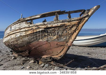 Old Abandoned Wooden Boat On The Beach, An Old Shipwreck Boat Abandoned Stand On Beach Or Shipwrecke