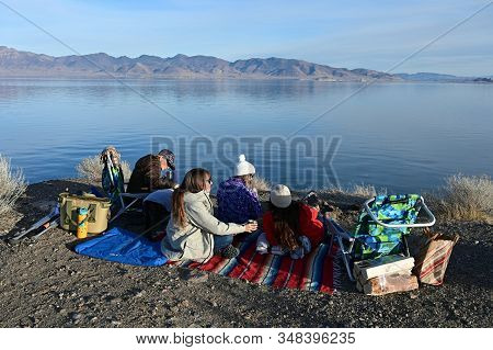 Pyramid Lake, Reno, Nevada - January 18, 2020: Young Women Enjoy Tranquil Afternoon With Their Dogs