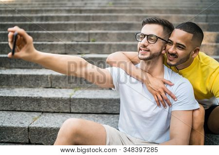Gay Couple Taking A Selfie With Mobile Phone.