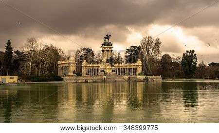 View Of The Monument Of Alfonso Xii From The Other Side Of The Pond, In The Retiro Park On A Cloudy