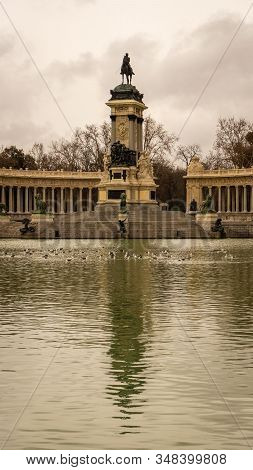 Close-up Of The Monument Of Alfonso Xii And Its Reflection In The Retiro Park On A Cloudy Winter Day