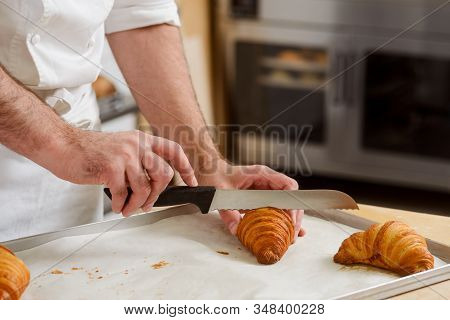 Man Is Cutting A Croissant With A Knife To Taste