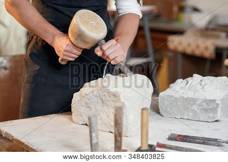 Bearded Craftsman Works In White Stone Carving With A Chisel. Creative Workshop With Works Of Art.