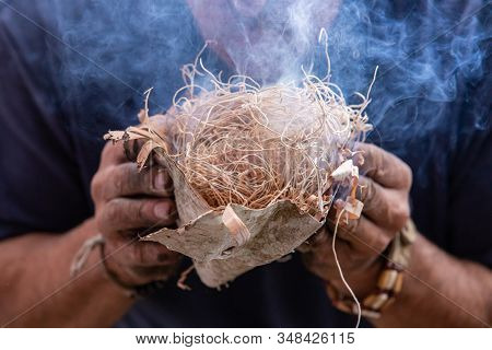 Closeup Of Man Hand Carrying Burning Smoky Straw Fire Start On Textured Wood During Demonstration Of