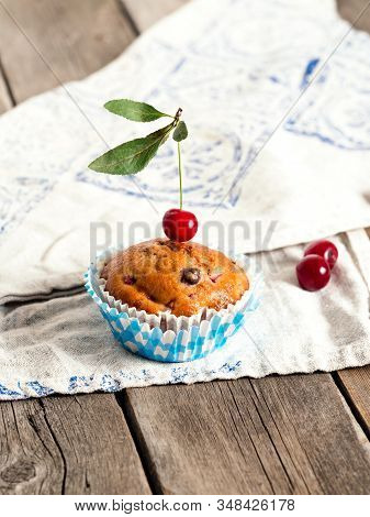 Freshly Baked Cherry Muffins With Fresh Berries On A Rustic Wooden Table