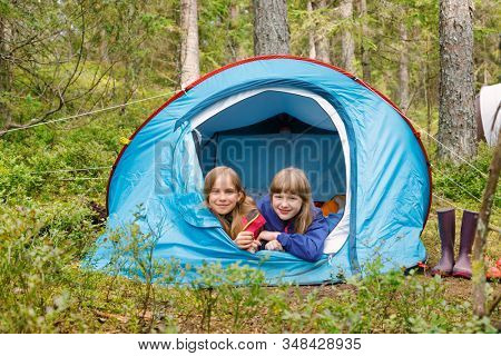 Tween girls lying together in tent enjoying camping in a summer forest during summer holidays