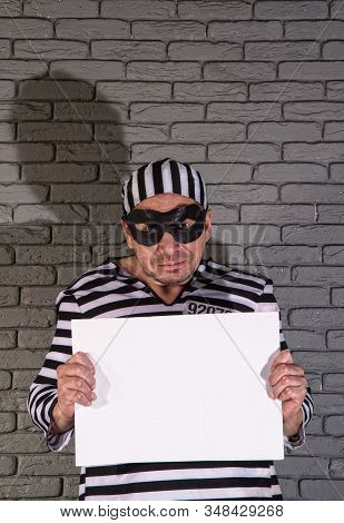 Funny Petty Crook In Exaggerated Clothes Of A Prisoner And A Black Mask With A Silly Face Holds An E