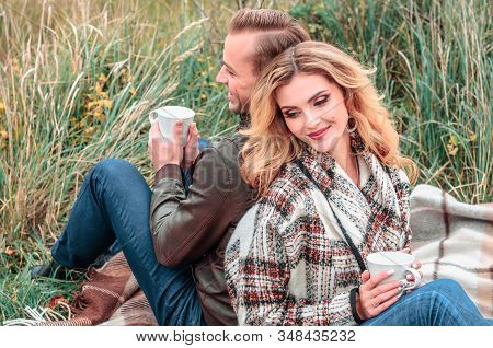 Young Couple In Love With Hot Drinks In Mugs Flirt Sitting Back To Back Outdoors, Concept Of The Beg