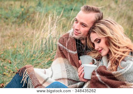 Young Romantic Couple In Love In A Gentle Hug Sitting Outdoors On A Cold Autumn Day, Drink Tea From