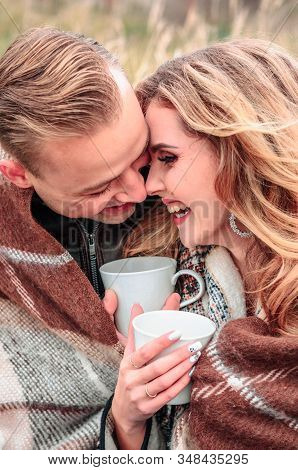 Young Couple In Love On A Date On An Outdoor Warm Themselves With A Hot Drink Of Tea In Cold Autumn
