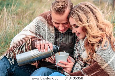 Happy Romantic Couple In Love Outdoors Wrapped In A Plaid Warm With Tea On A Cold Autumn Day, The Gu