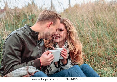 Young Couple In Love With A Hot Drink In Their Hands Flirts Outdoors