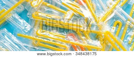 Pile Of Yellow Drinking Straws On A Blue Background. Top View Of Many Plastic Bendy Cocktail Straws,
