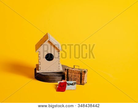 Wooden Bird House With Suitcase, Map, Pasport And Ticket On A Bright Yellow Background. A Small Blac