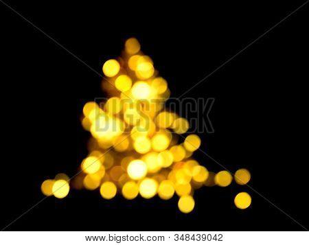 Defocused Shiny Evergreen Tree Shape. Holiday Bokeh Golden Lights Background. Festive Backdrop. Desi