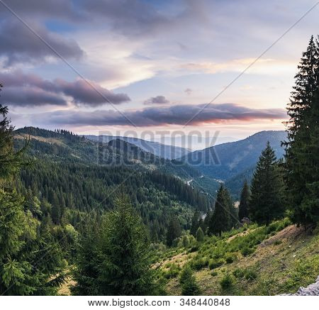Summer Mountains Landscape In Transilvania, Romania. Distant Mountain Range And Thin Layer Of Fog On